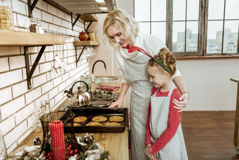 Señora rubia agradable que muestra sus galletas completamente listas de la hija fotos de archivo libres de regalías