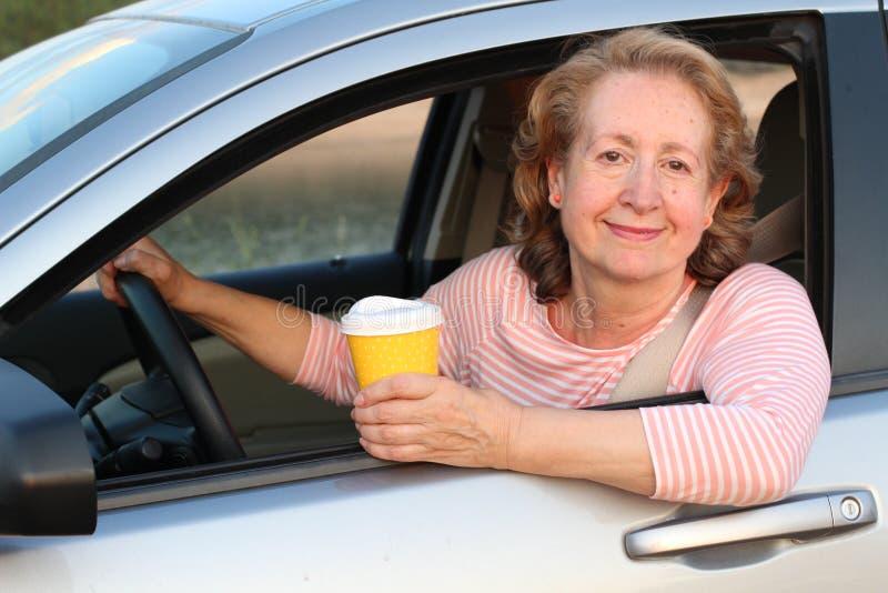 Señora rubia madura que conduce con café foto de archivo