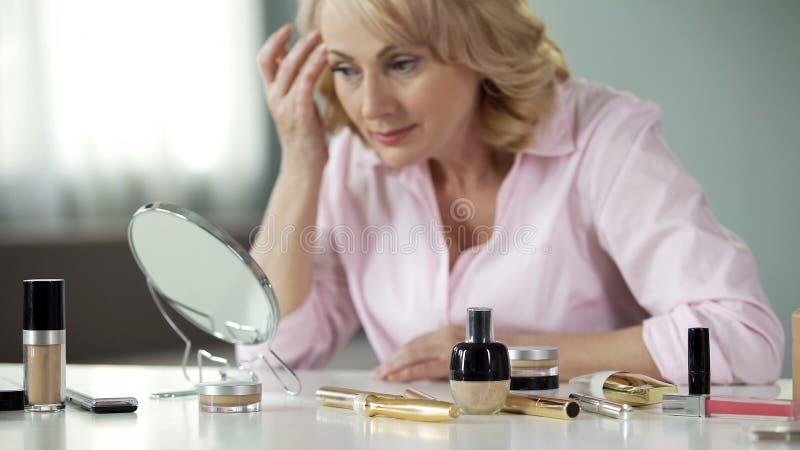 Señora satisfecha con color y la elasticidad de los gracias de la piel a los cosméticos de la innovación fotos de archivo