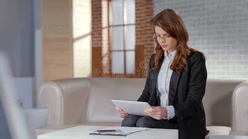 Señora seria del negocio en vidrios usando la tableta para el trabajo, informes de la compañía de la lectura fotografía de archivo libre de regalías