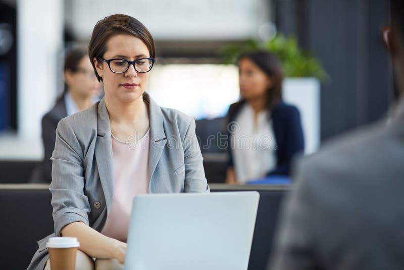 Señora seria que analiza informe de ventas sobre el ordenador portátil imágenes de archivo libres de regalías