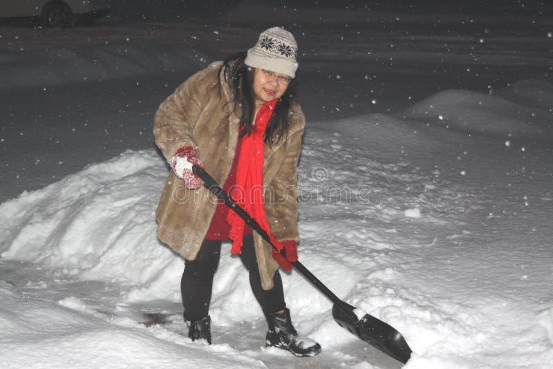 Señora Shoveling Snow imágenes de archivo libres de regalías