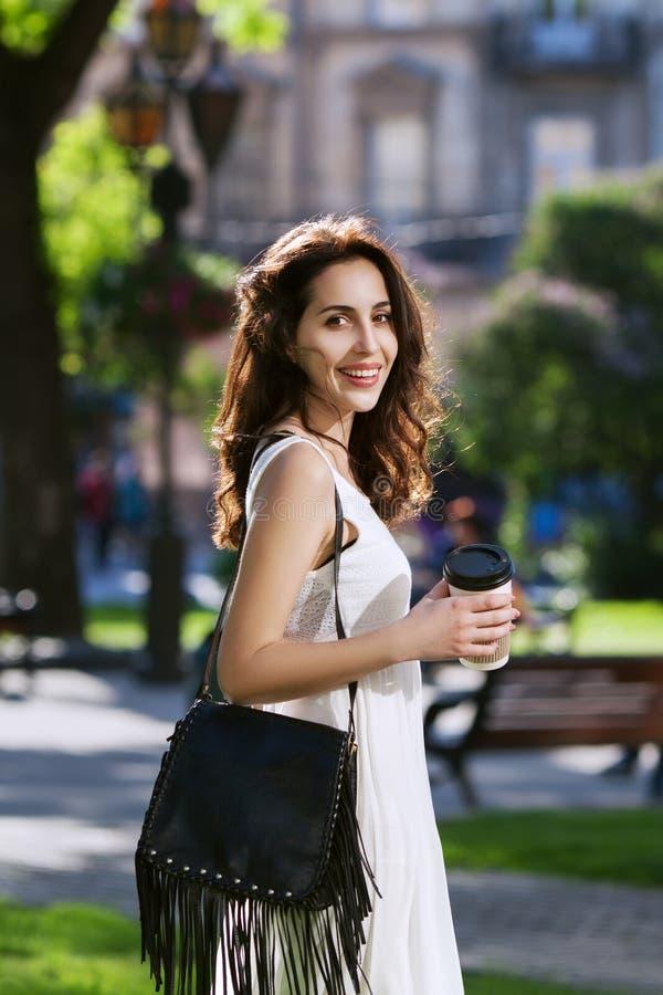 Señora sonriente feliz hermosa joven que camina en la calle, sosteniendo la taza de café de papel Ropa elegante que lleva modelo  fotografía de archivo libre de regalías