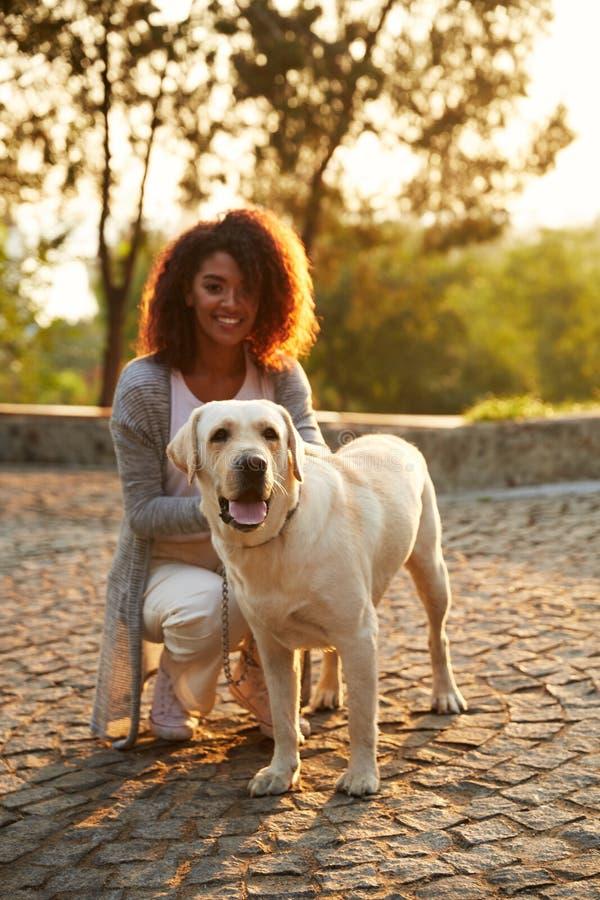 Señora sonriente joven en la ropa casual que sienta y que abraza el perro en parque imagenes de archivo