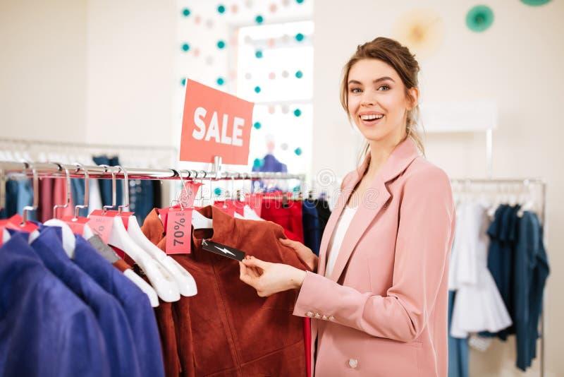 Señora sonriente que encuentra algo en venta en tienda de la ropa imagen de archivo