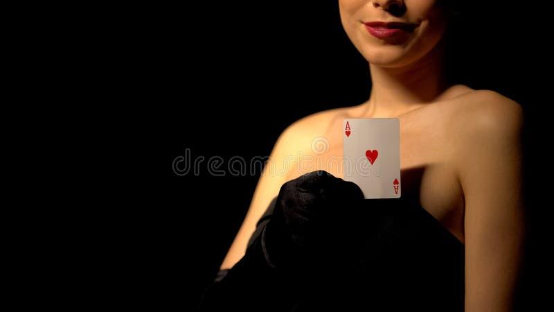 Señora sonriente que muestra el as de corazones en la cámara, el póker y la veintiuna, casino imagenes de archivo