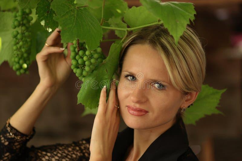 Señora y uvas fotografía de archivo