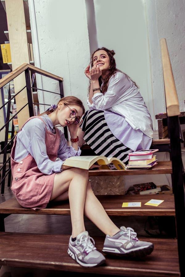Señoras de moda aptas que están ocupadas con literatura de la librería fotografía de archivo libre de regalías