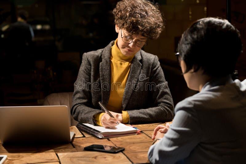 Señoras del negocio que escriben el plan del trabajo en oficina oscura imágenes de archivo libres de regalías