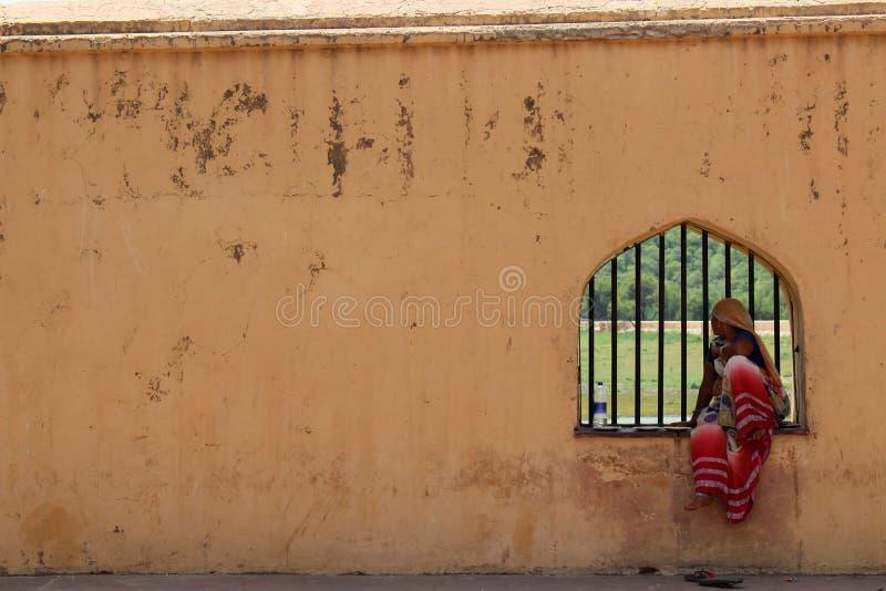 Señoras indias locales que se sientan en una ventana en Amber Amer Fort de foto de archivo