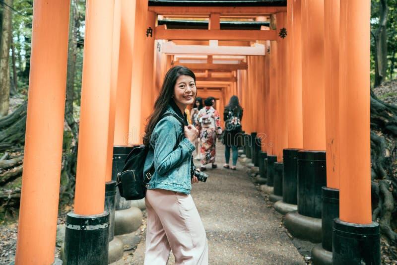 Señoras japonesas en kimono que caminan debajo de torii imagen de archivo