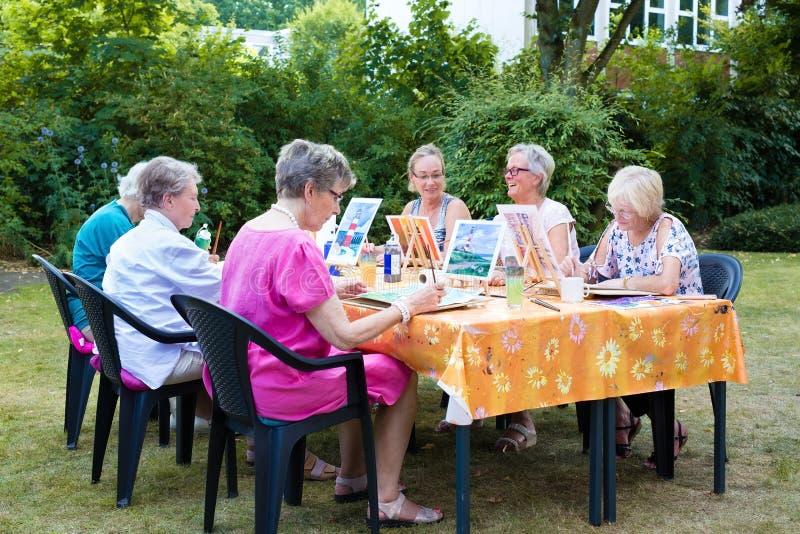 Señoras mayores que asisten a las clases de arte al aire libre asentadas alrededor de una tabla que trabaja en sus pinturas usand imágenes de archivo libres de regalías