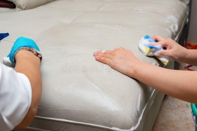 Señoras que limpian el sofá de cuero imagen de archivo libre de regalías
