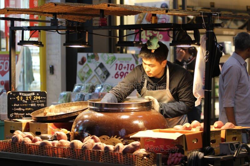 Seúl, Corea del Sur/31 03 2018: Vendedor de comida de la calle que limpia un tarro grande debajo de las lámparas en Myeong-Dong imagen de archivo libre de regalías