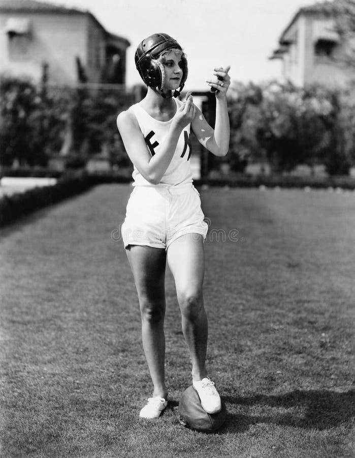 Se bra för laget, en ung kvinna i en fotbollhjälm som ser in i en spegel och sätter på sminket (alla visade personer arkivfoto