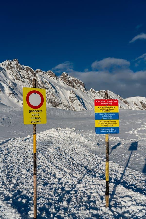 Se connecte des voies d'un groomer de neige devant la région de chasse de Graue Hörner en Suisse photos libres de droits