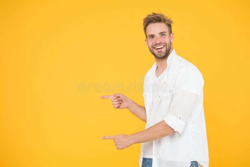Se d?r Man som pekar p? kopieringsutrymme Kontrollera detta ut Muskulös stilig le orakad grabb för man på gul bakgrund fotografering för bildbyråer