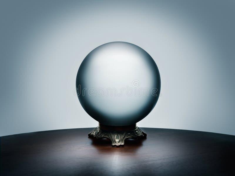 Se din framtid i den magiska kristallkulan på den enkla mörka trätabellen royaltyfria bilder