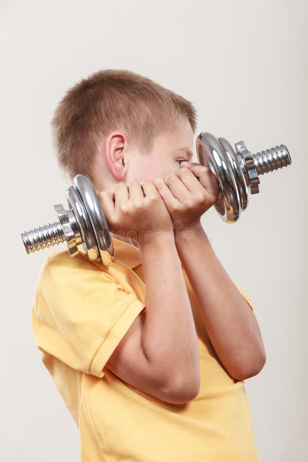 Se divierte al muchacho que hace ejercicio con pesa de gimnasia imagen de archivo