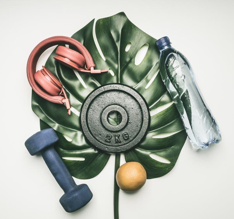 Se divierte el concepto, pesas de gimnasia, botella de agua, naranja, auriculares para entrenar, en una hoja tropical en una ende fotos de archivo libres de regalías