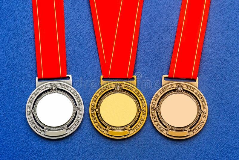 Se divierte la medalla con la cinta roja, oro, plata, bronce en un CCB azul imagenes de archivo