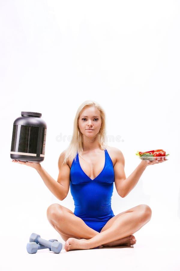 Se divierte a la muchacha con la ensalada, una poder de una proteína y pesas de gimnasia fotografía de archivo