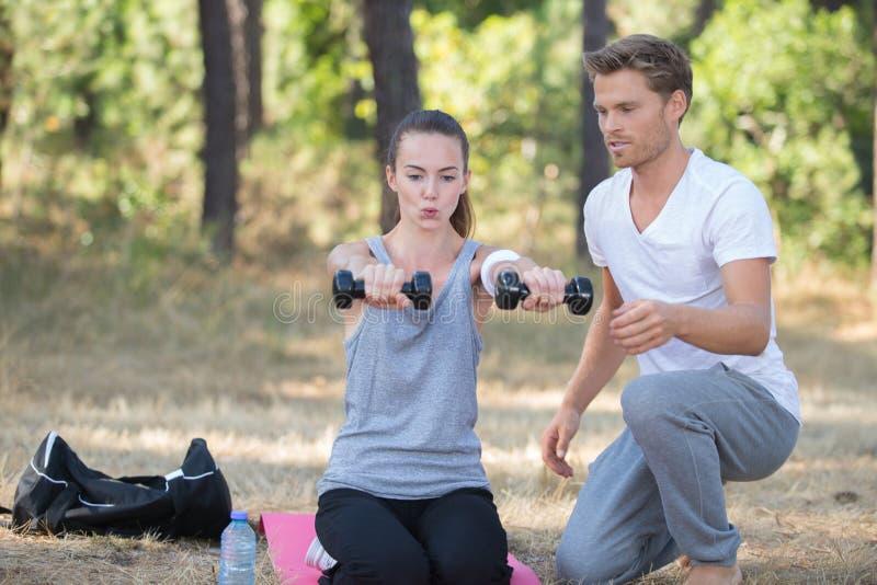 Se divierte a la muchacha que hace ejercicios con el novio al aire libre fotografía de archivo libre de regalías