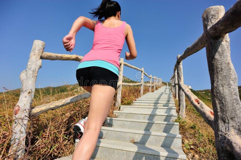 Se divierte a la mujer que corre en las escaleras de la montaña imágenes de archivo libres de regalías