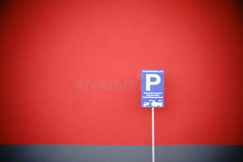 Se garer se connectent le mur rouge photographie stock