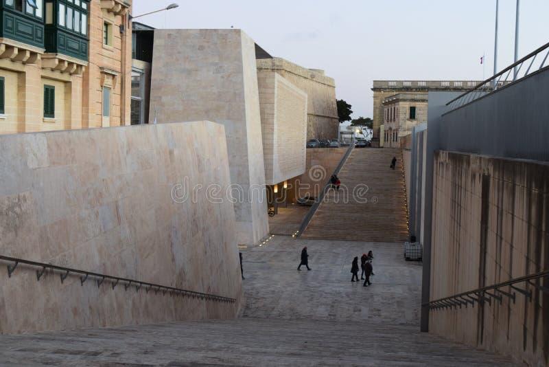 Se ner från mur med tinnarvallen på ingången till Valletta med folk som ut går royaltyfri foto