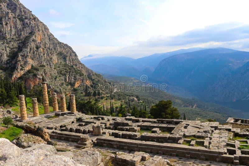 Se ner på templet av Apollo i ancint Delphi Greece och på fristaden av Athena ner kullen med olivträd och mis arkivfoto