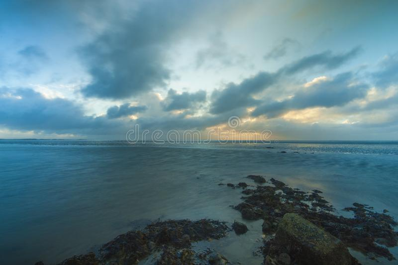 Se nubl? en parte salida del sol sobre las aguas, los mudflats y las rocas de marea fotografía de archivo libre de regalías