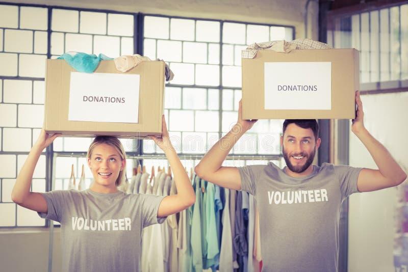 Se ofrece voluntariamente las cajas de la donación que llevan en la cabeza fotos de archivo