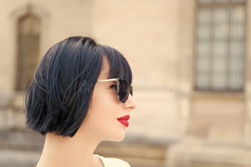 Se?ora de moda de la muchacha con el fondo urbano al aire libre de la arquitectura del peinado de la sacudida Presentaci?n de mod fotografía de archivo