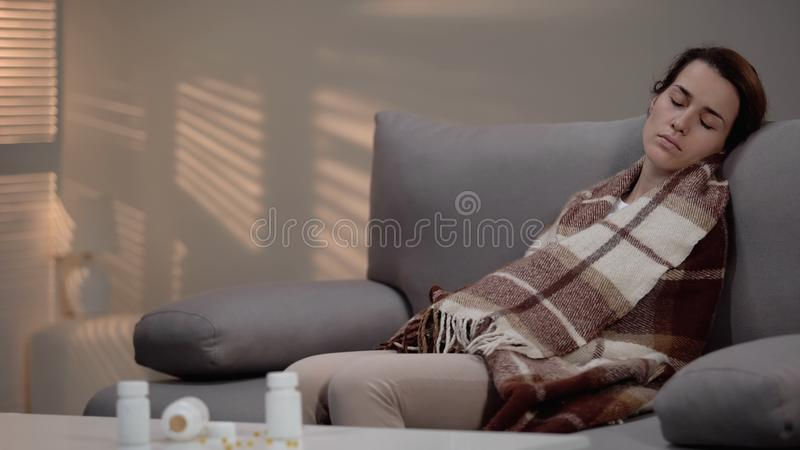 Se?ora deprimida joven que miente en el sof? despu?s de tomar a demasiado las p?ldoras, tentativa del suicidio foto de archivo