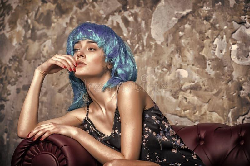 Se?ora en la cara pensativa que presenta en la peluca azul, fondo del muro de cemento La mujer con el pelo azul parece unordinary imágenes de archivo libres de regalías