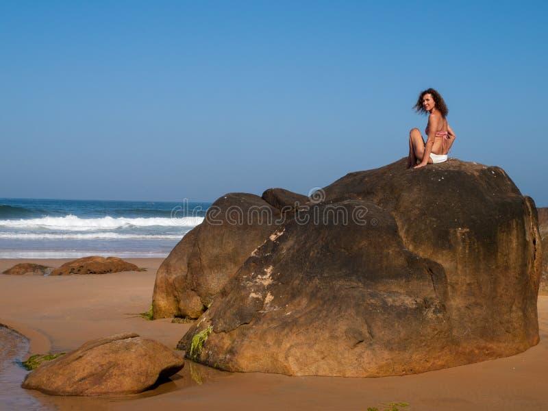 Se?ora en la roca del mar fotografía de archivo