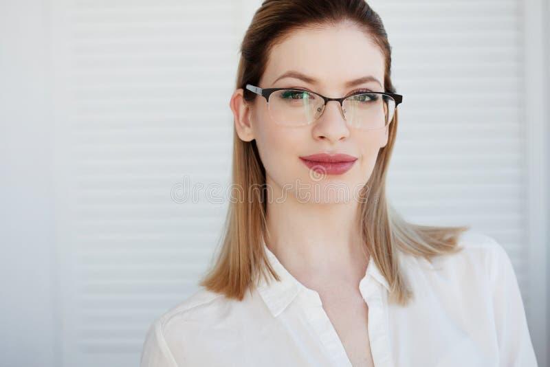 Se?ora joven del negocio en la camisa y los vidrios blancos Sonrisa atractiva de la mujer joven imagenes de archivo