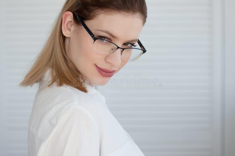 Se?ora joven del negocio en la camisa y los vidrios blancos Sonrisa atractiva de la mujer joven imagen de archivo