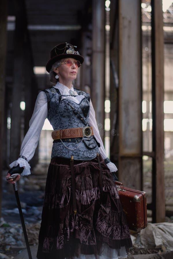 Se?ora mayor en un traje del steampunk en una f?brica abandonada con los brazos a disposici?n foto de archivo