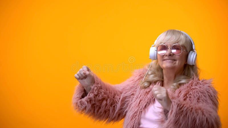 Se?ora mayor positiva en capa rosada y gafas de sol redondas que escucha la m?sica imagen de archivo