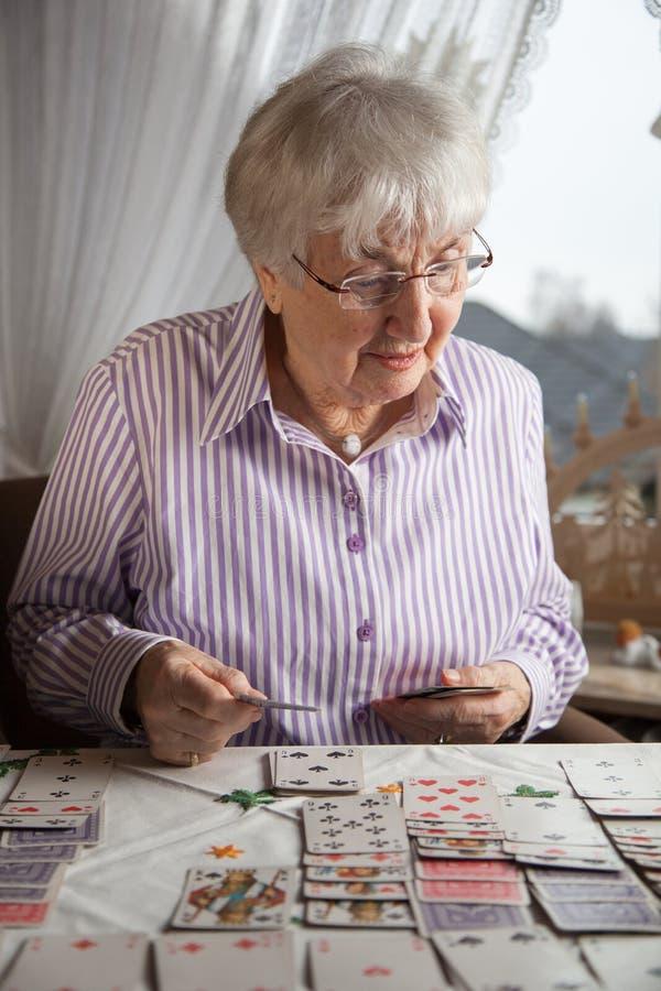 Se?ora mayor que juega tarjetas del solitario en casa fotos de archivo libres de regalías