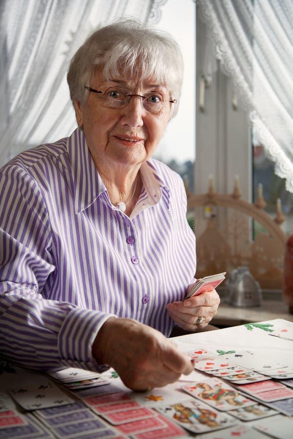 Se?ora mayor que juega tarjetas del solitario en casa imágenes de archivo libres de regalías