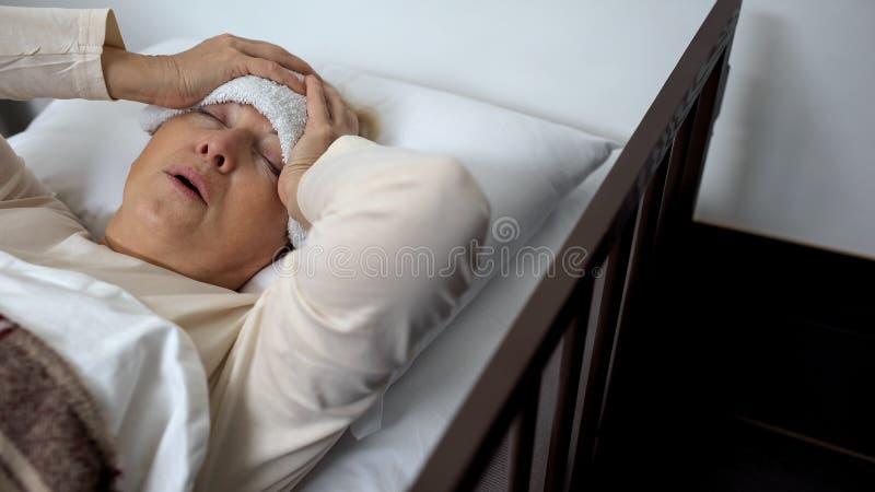 Se?ora mayor que miente en cama con la compresa de la frente y el dolor de cabeza terrible sufridor imagen de archivo