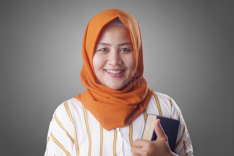 Se?ora musulm?n feliz con el libro fotos de archivo