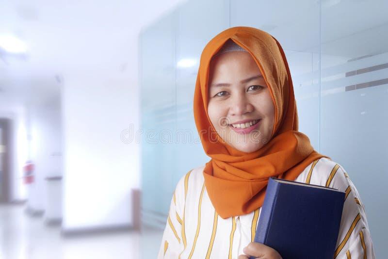 Se?ora musulm?n feliz con el libro fotografía de archivo