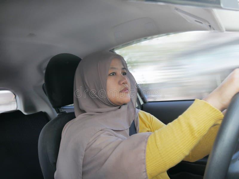 Se?ora musulm?n sonriente Driving un coche imagen de archivo libre de regalías