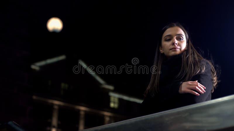 Se?ora pensativa que piensa en los problemas del trabajo, coloc?ndose en la calle de la ciudad de la noche solamente imagenes de archivo