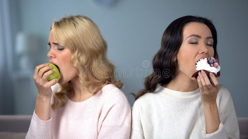 Se?ora que goza de la torta, amigo femenino que come la manzana, opci?n individual de la comida apropiada imagen de archivo libre de regalías