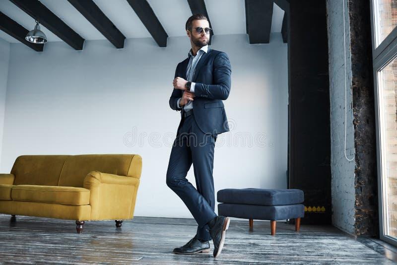 Se precis perfekt Full längdstående av den unga stilfulla affärsmannen i dräkten som står i ett modernt kontor arkivbilder